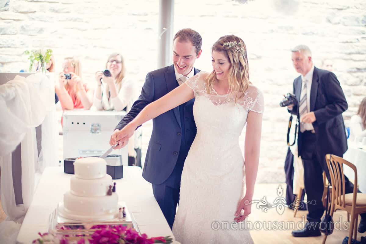 cutting the cake at Durlston castle wedding