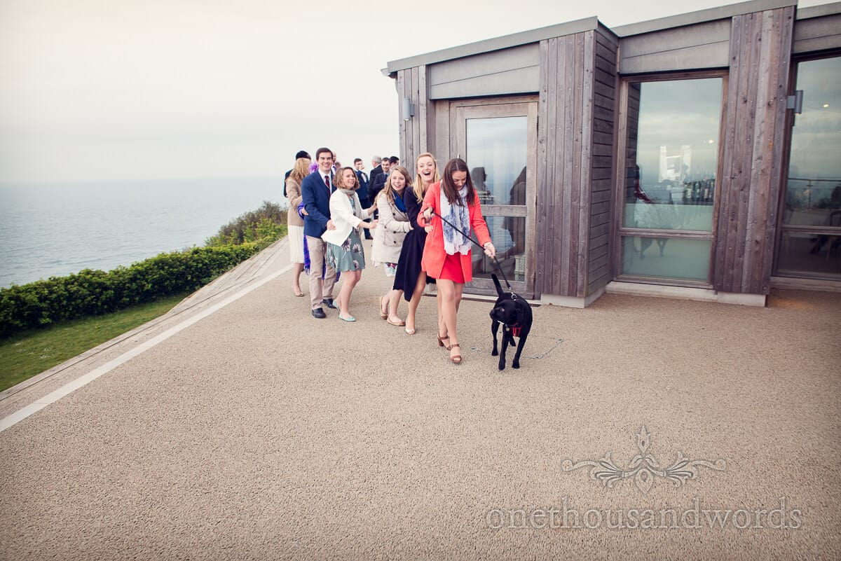 Conga line with dog at Durlston Castle wedding