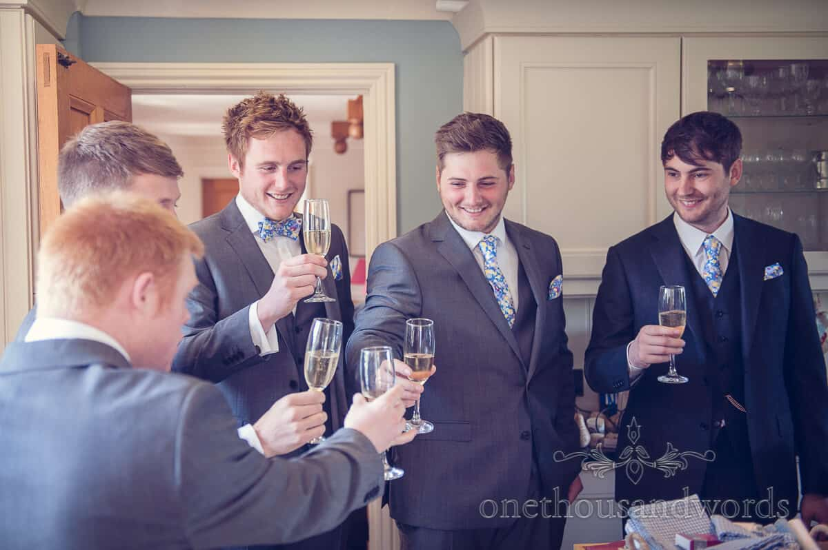groom and groomsmen enjoy champagne on wedding morning
