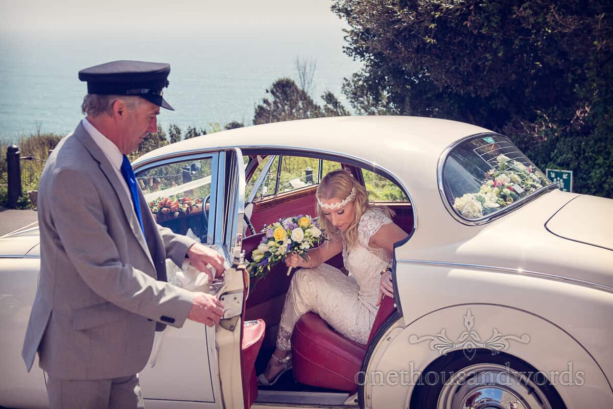 Bride exits wedding car at Durlston Castle wedding venue