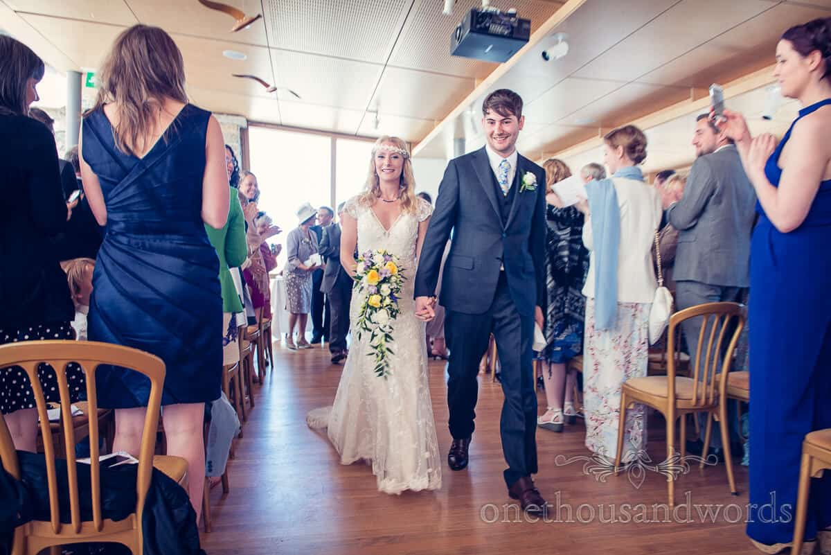 Bride and groom walk down aisle at Durlston Castle