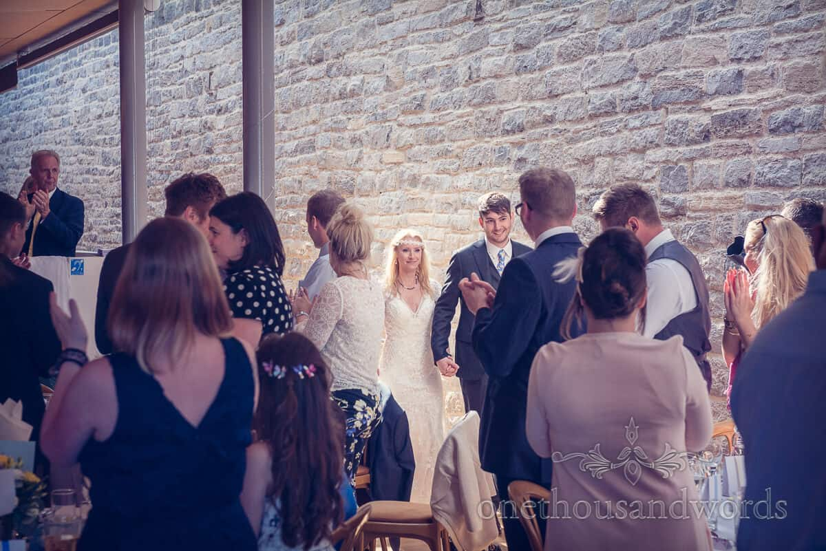 bride and groom enter wedding breakfast at Durlston Castle