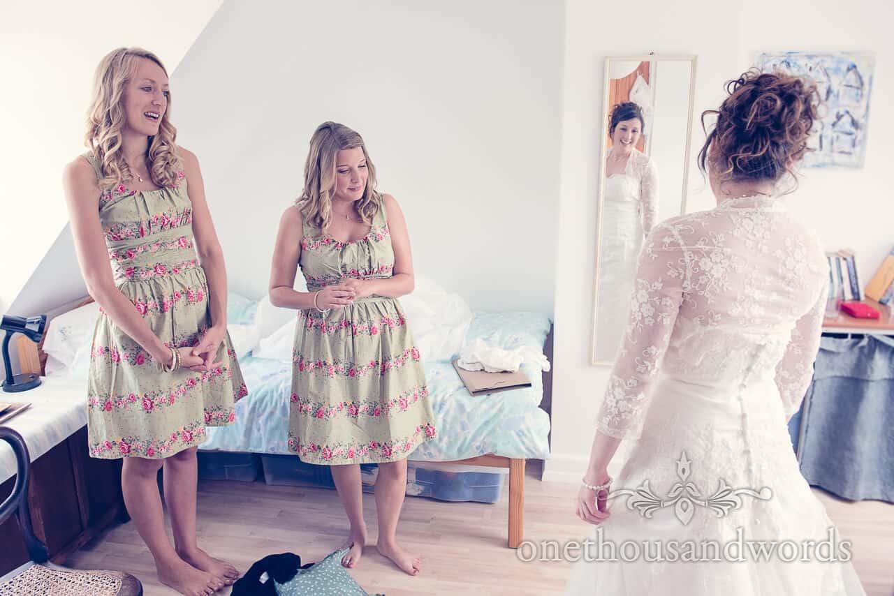 Bridesmaids admire bride in wedding dress