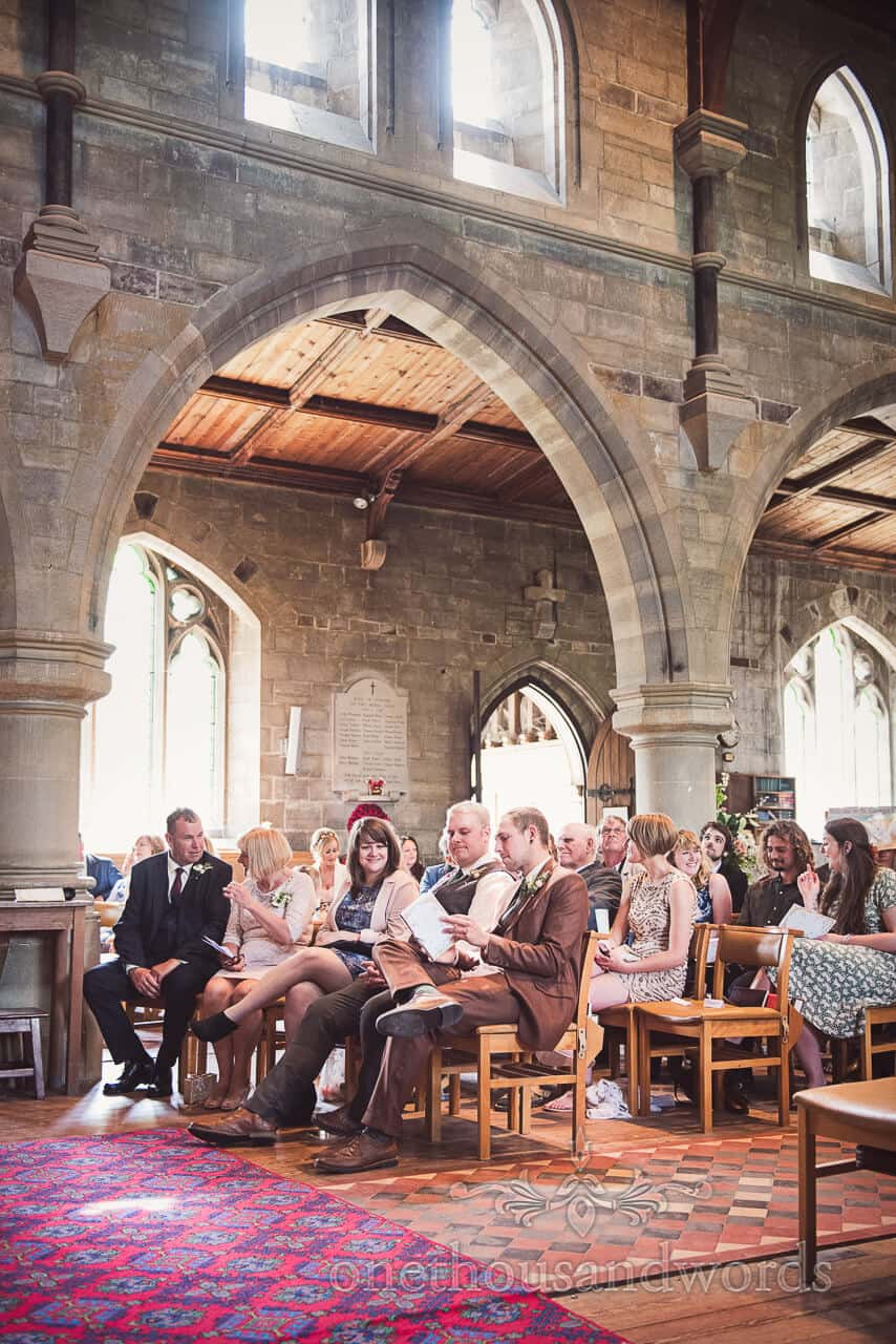 Groom and guests wait in English stone church wedding
