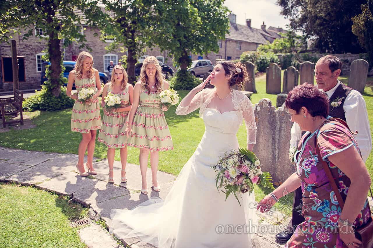 Bride blows kiss with bridesmaids outside country church