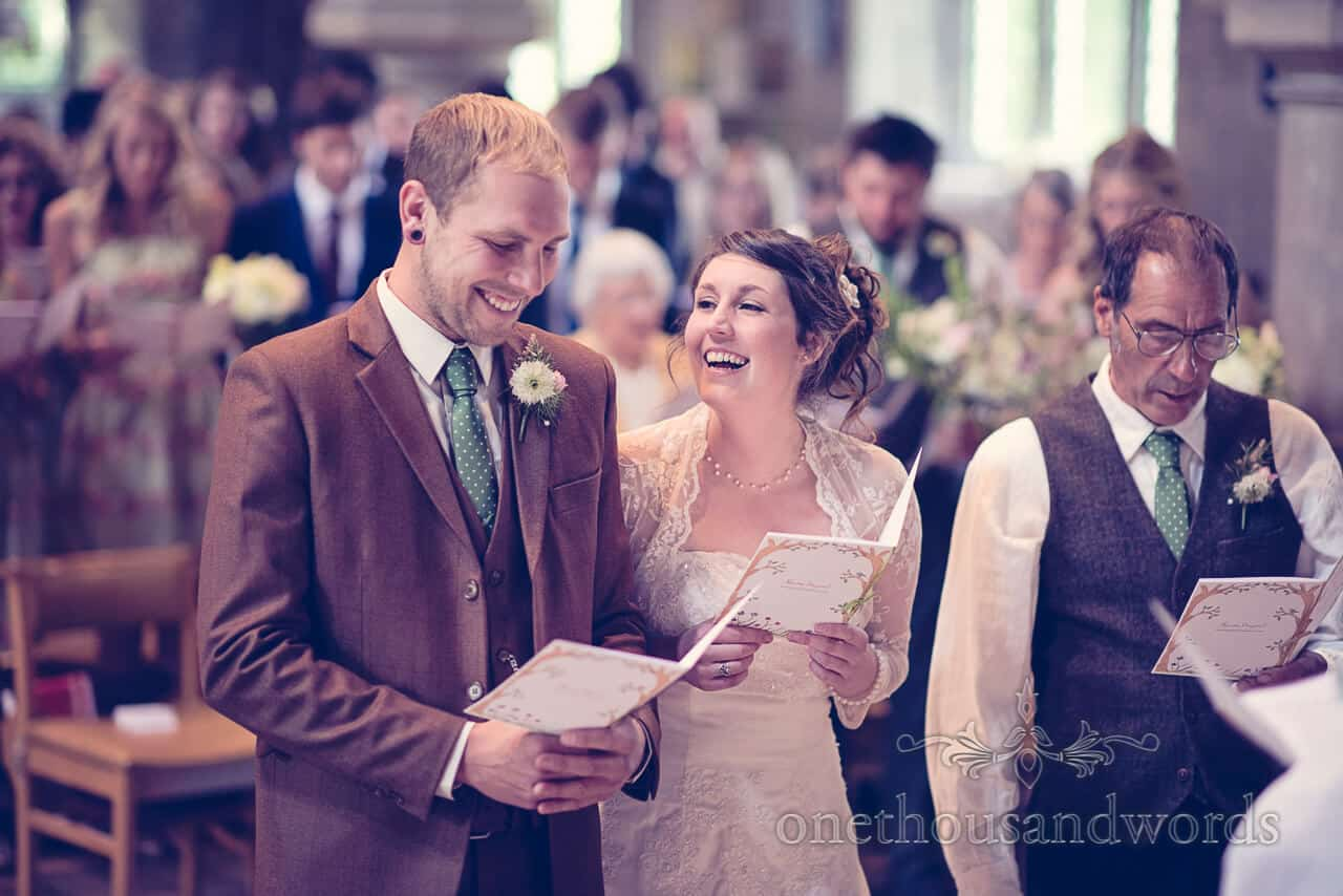 Bride and groom laugh during country church wedding service