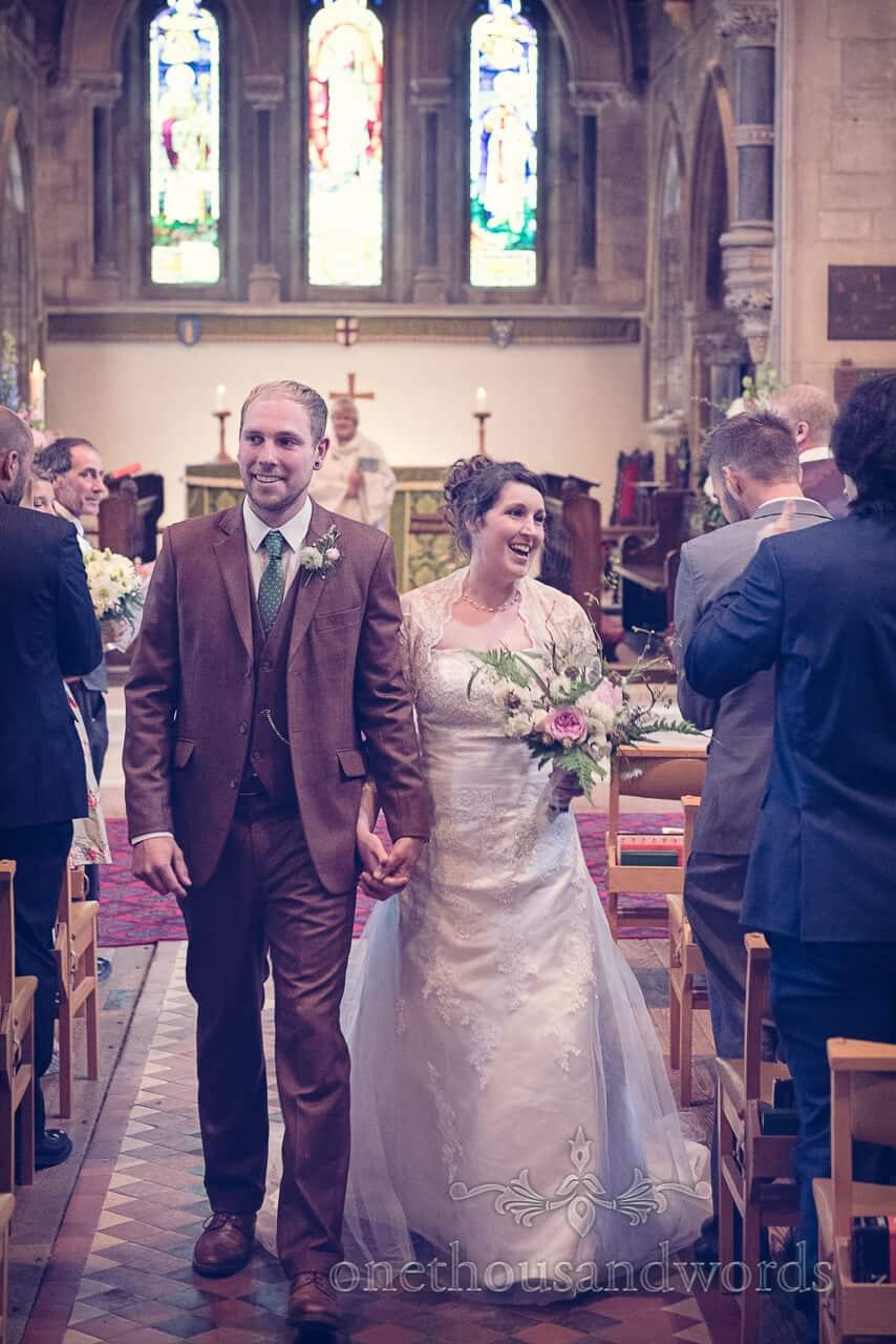 Bride and groom leave english stone church wedding