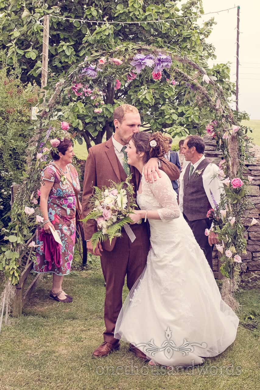 country wedding photographs kiss under floral archway