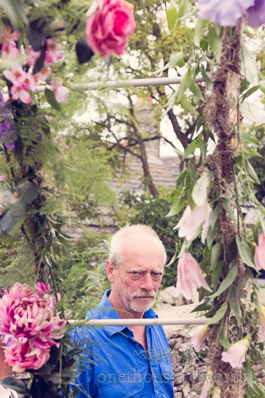 Grumpy looking wedding guest with pink flowers