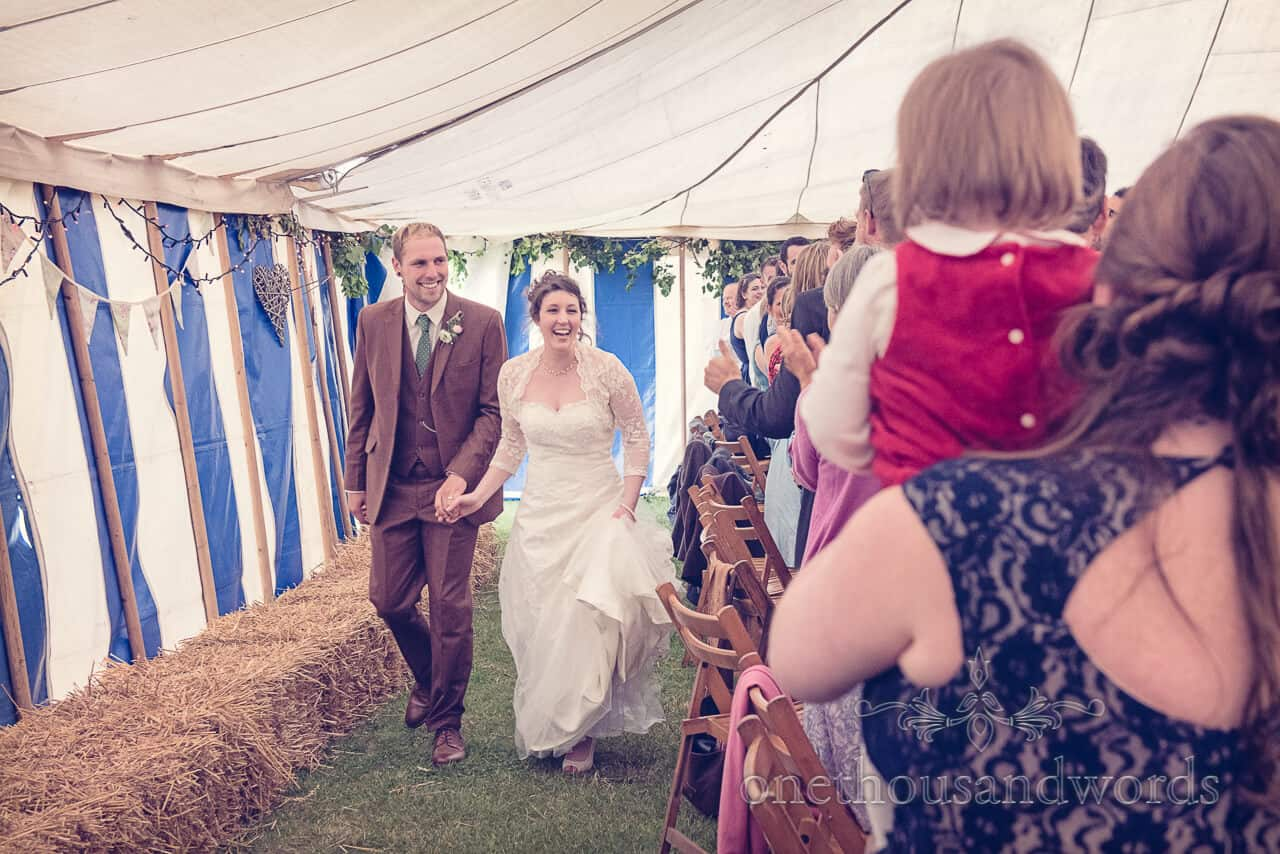 bride and groom enter country wedding marquee