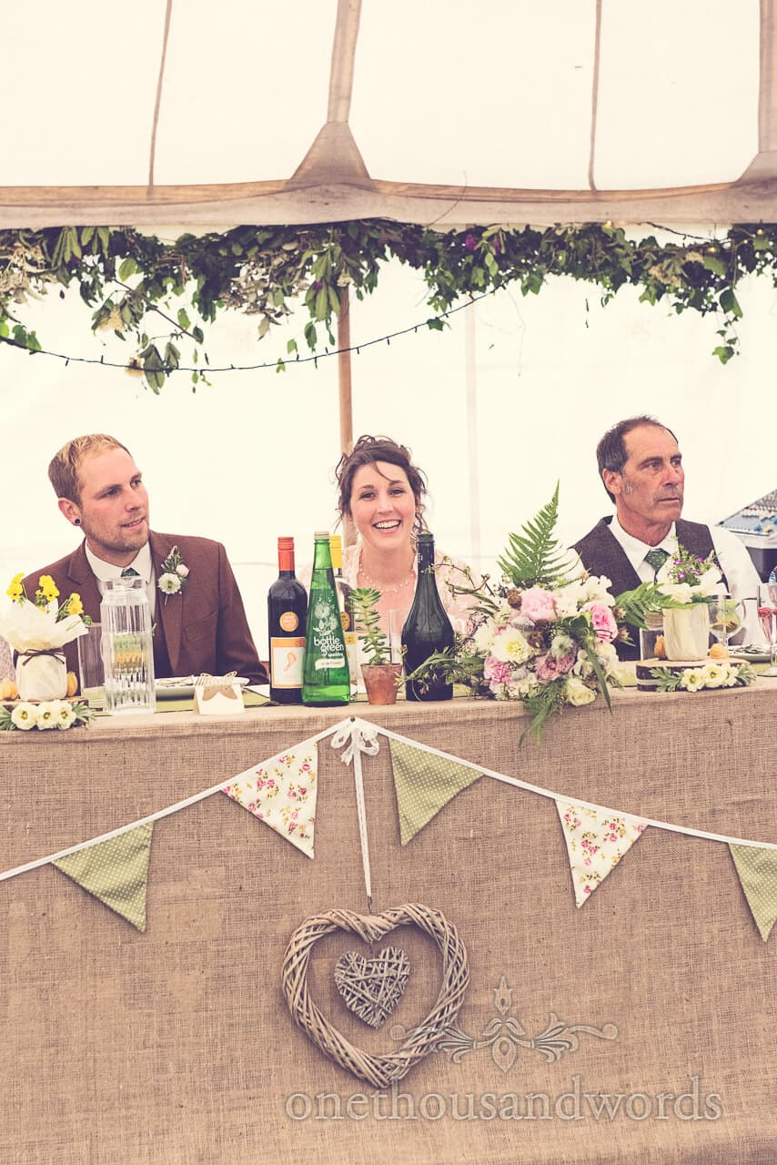 Bride portrait at country wedding top table with wicker love hearts