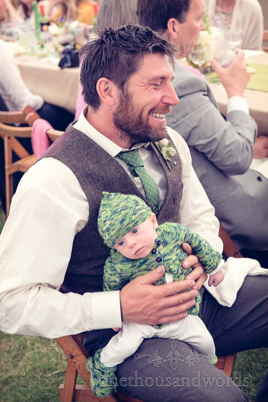 Baby at country wedding with father in waist jacket