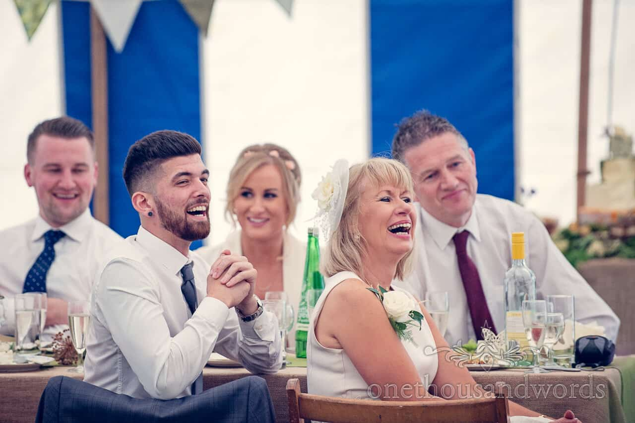 Wedding guests laugh at wedding speeches