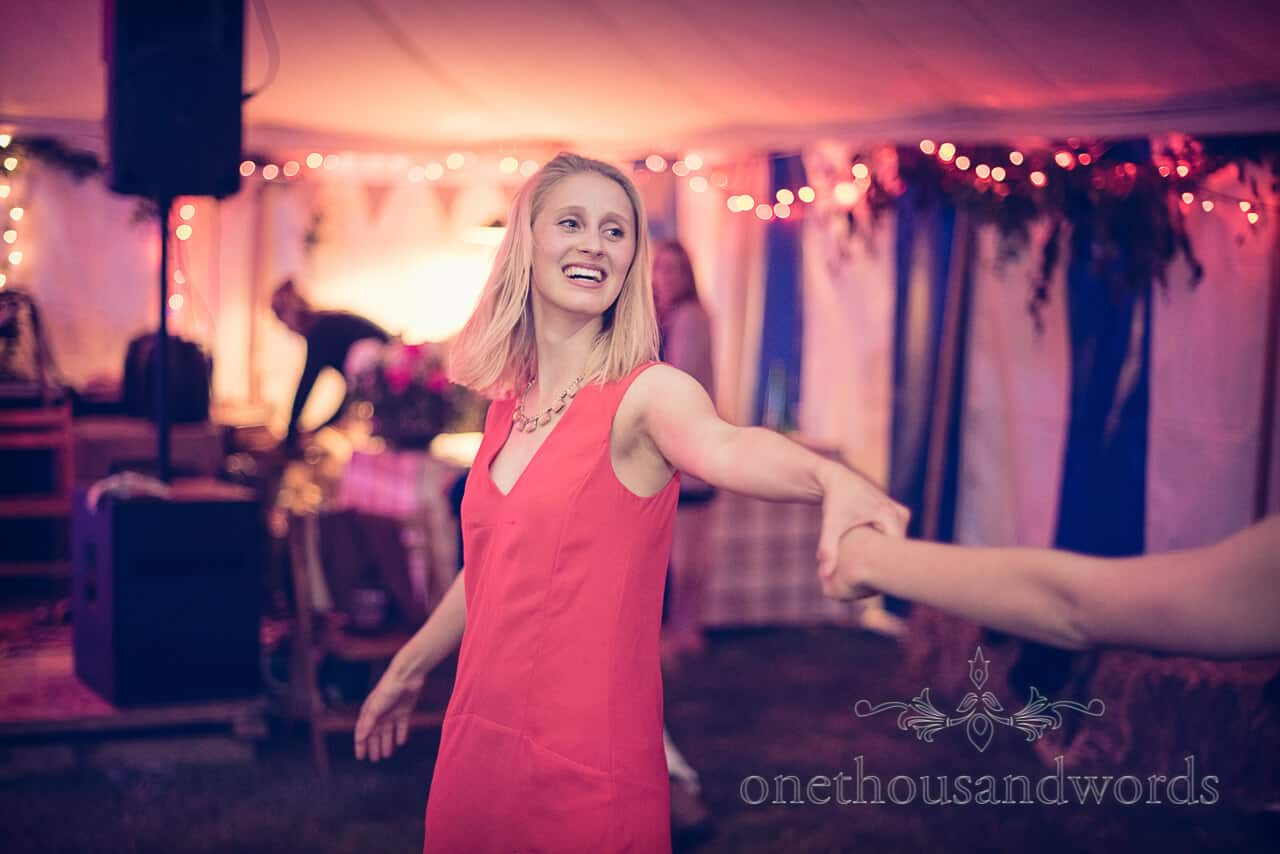 Wedding guest in red dress dancing in country marquee