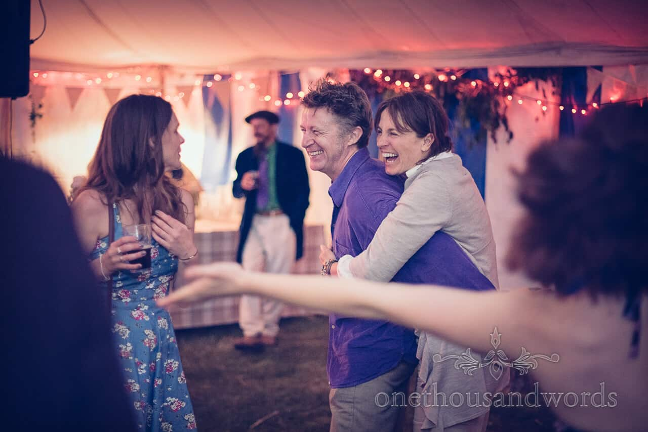wedding guests hug and laugh on wedding evening