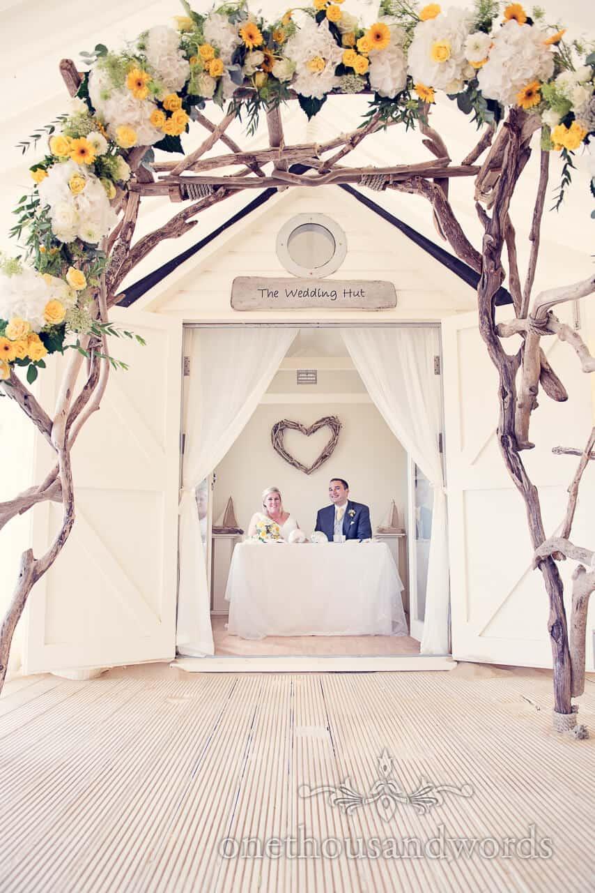 Beach wedding Bournemouth wedding hut and flower arch