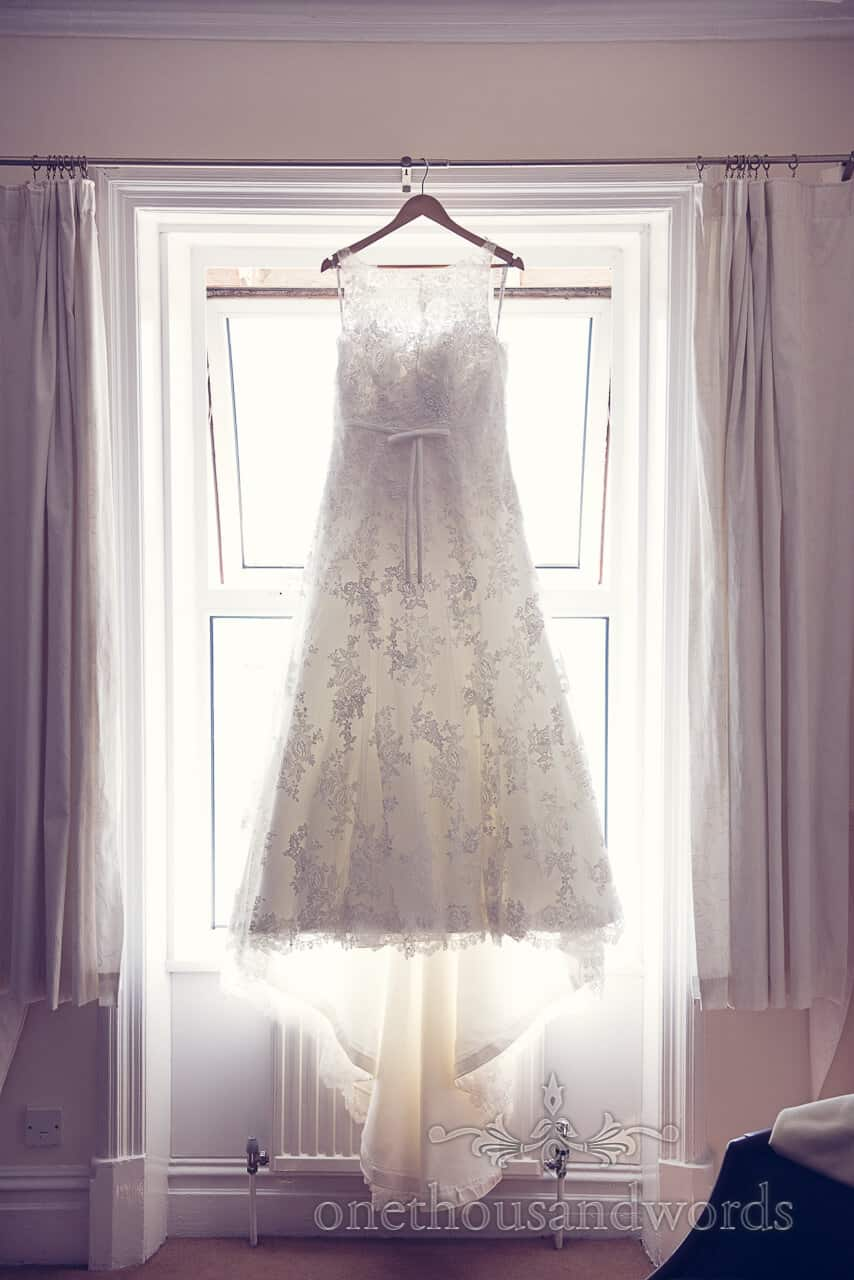 Weddign dress with ivory lace detail hanging in window