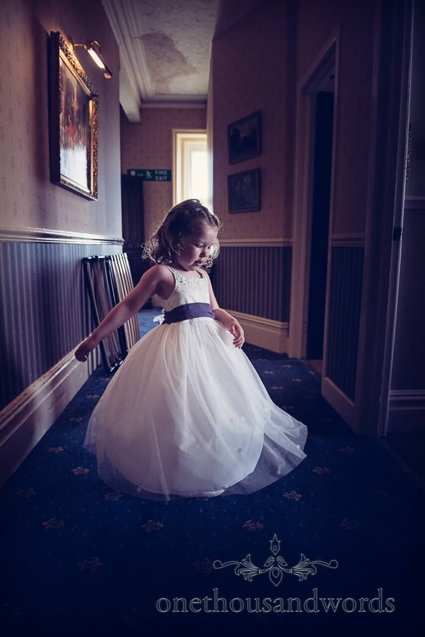 Flowergirl in white dress with purple sash