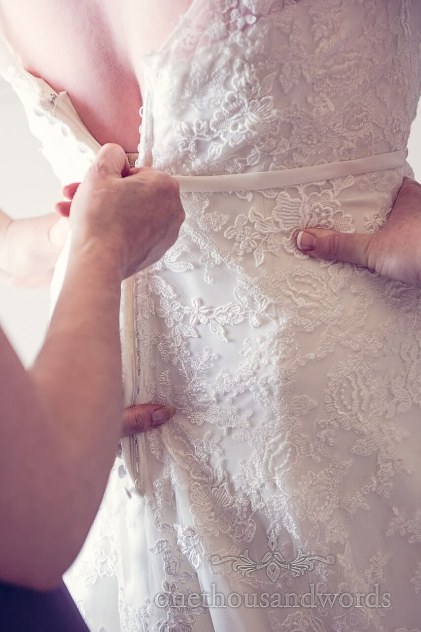 Bride is buttoned into her wedding dress