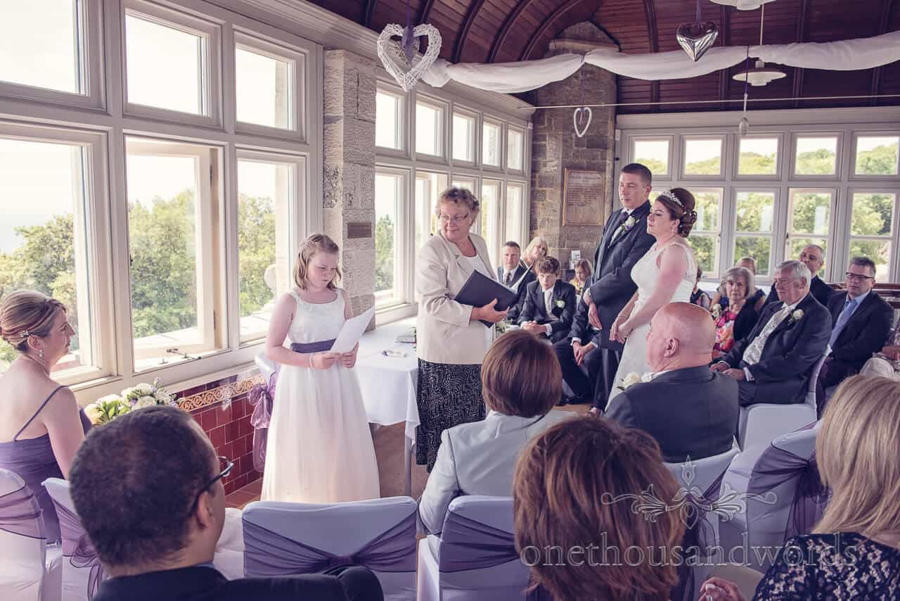 Flower girl reading at Durlston Castle wedding ceremony