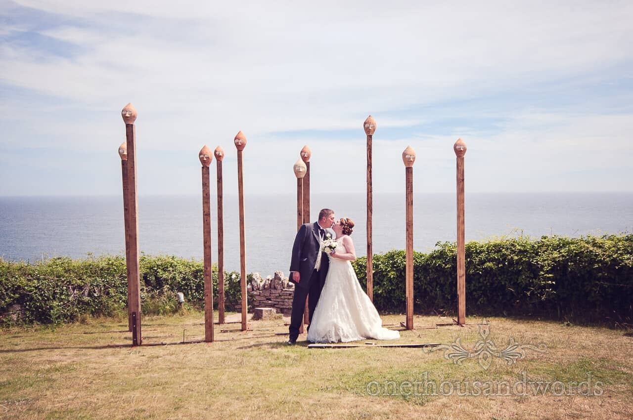 Bride and groom kiss in art instillation at Durlston Castle