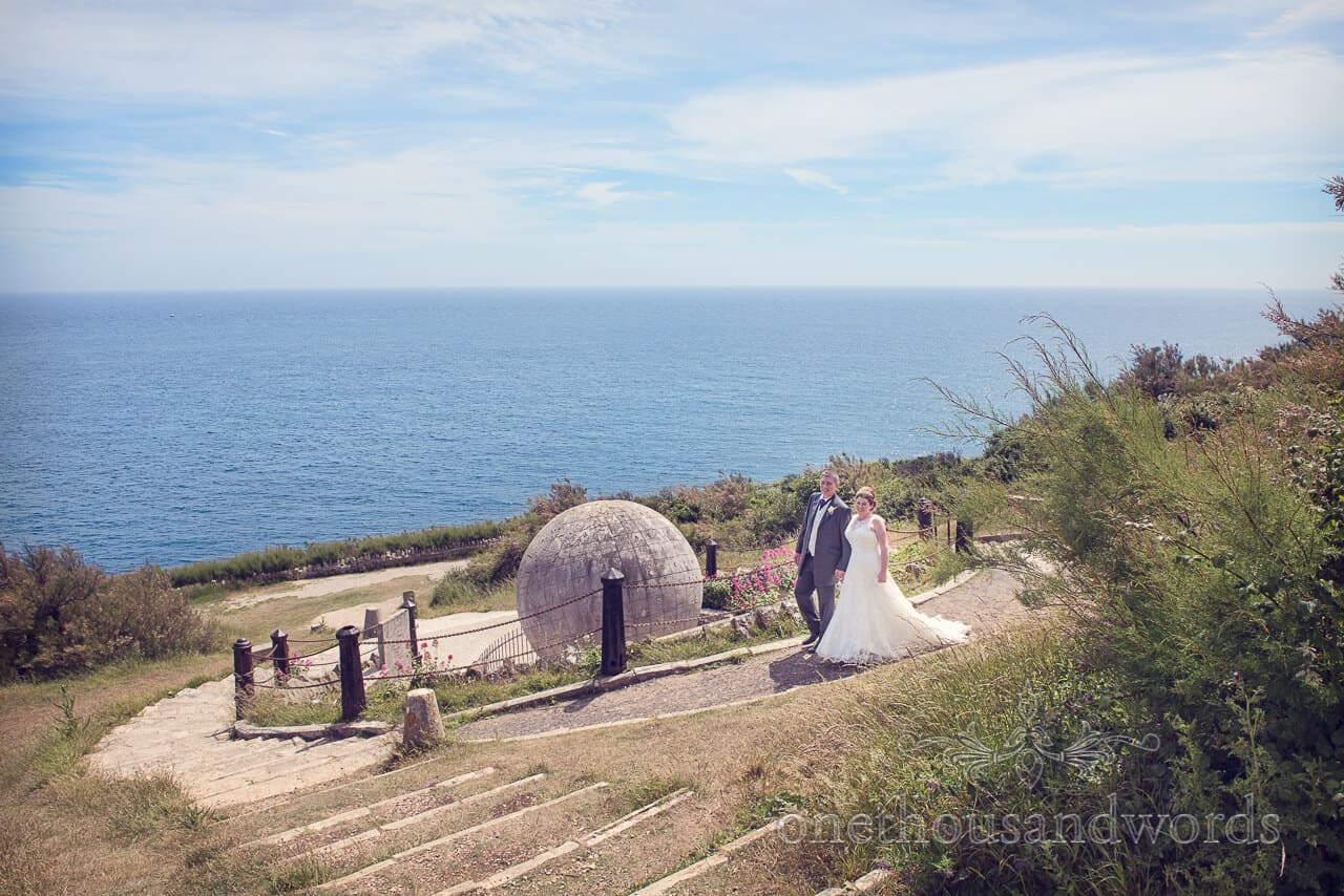 Bride and groom by the sea with Victorian stone globe
