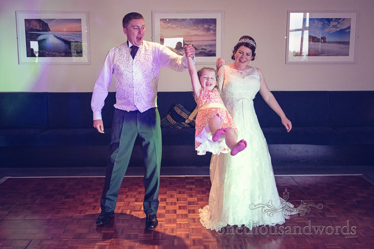 Bride and groom swing daughter at Grand Hotel Swanage wedding