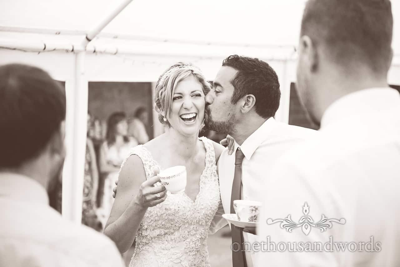 Black & White wedding guest kisses bride with tea