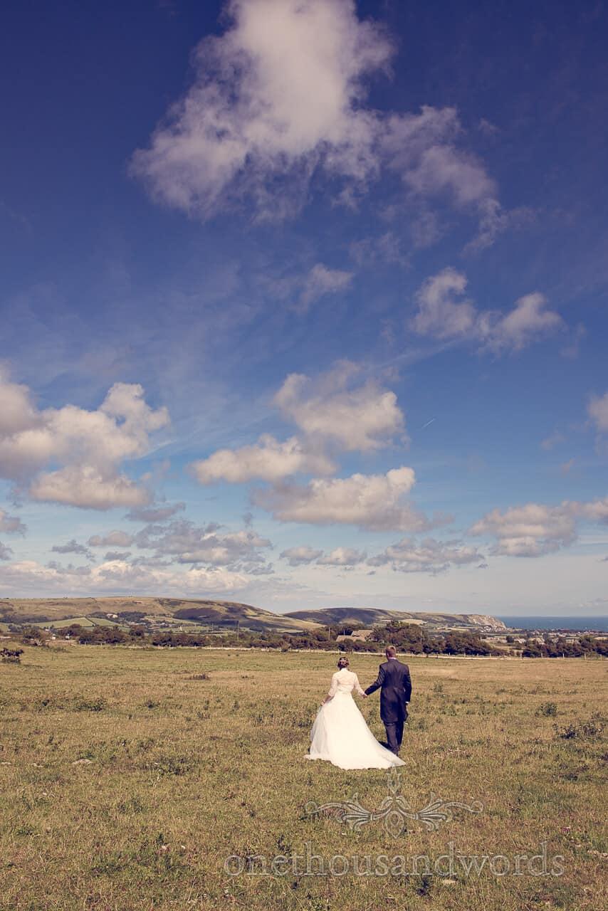 bride and groom walk through Dorset countryside