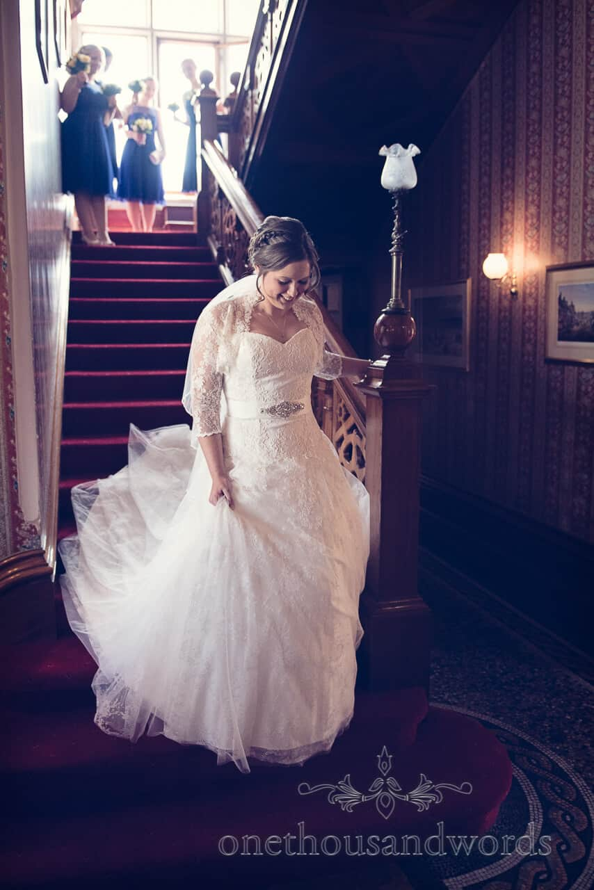 Bride descends wooden staircase at Purbeck House Hotel Wedding