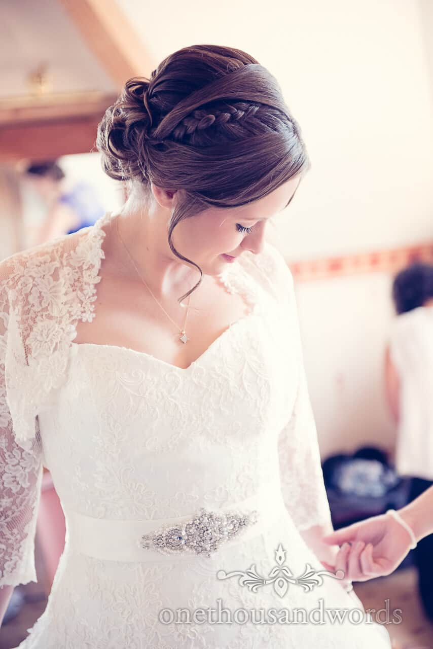 bride in lace detail and diamonte wedding dress with hair plait