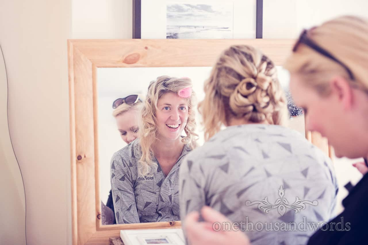Bride looks in mirror on morning of wedding in Dorset