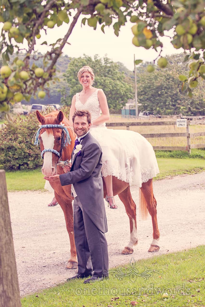 Bride on Horse with Groom at Countryside Wedding