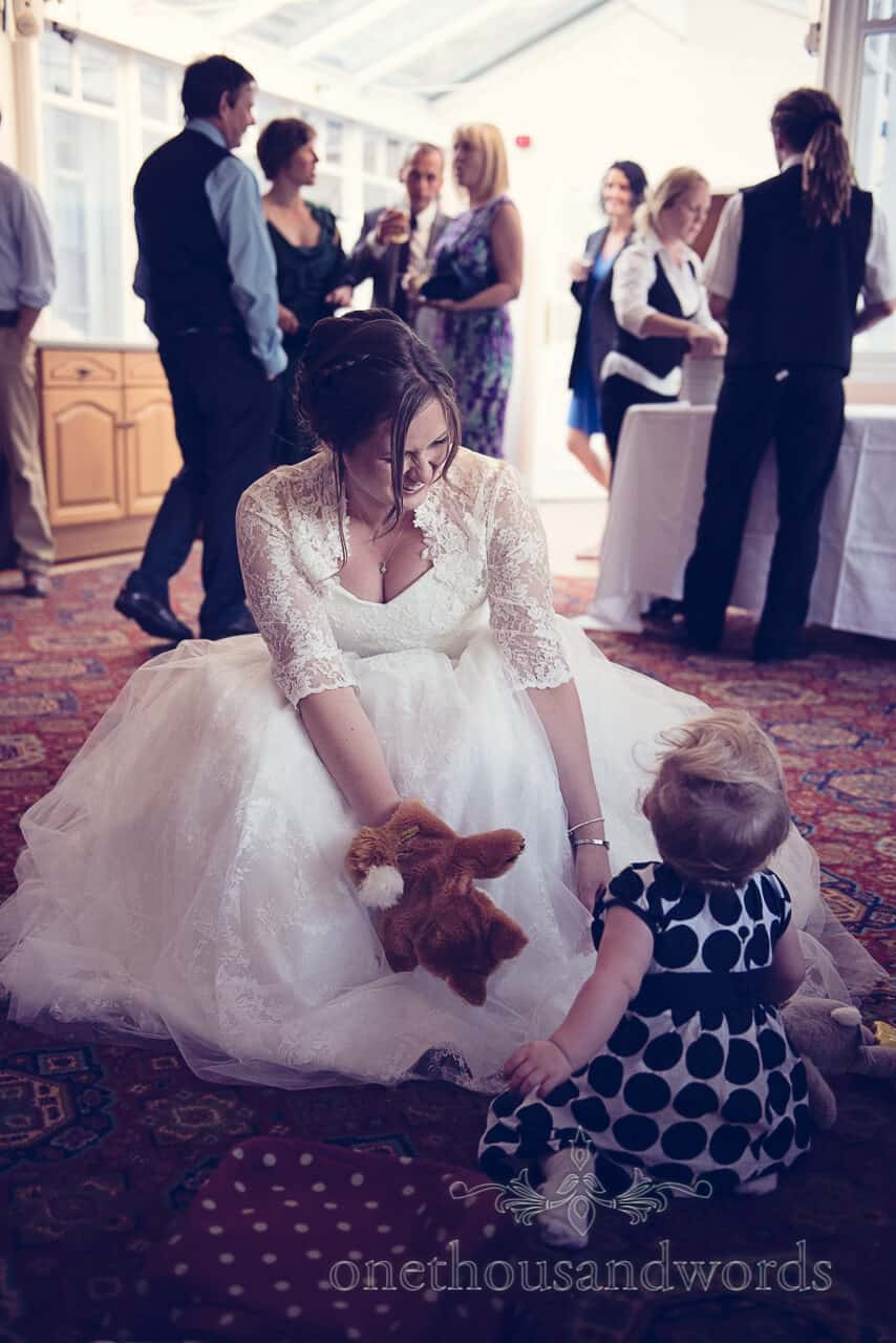 bride plays with child wedding guest