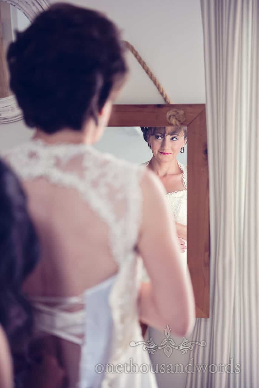 Bride portrait in mirror whilst getting into wedding dress