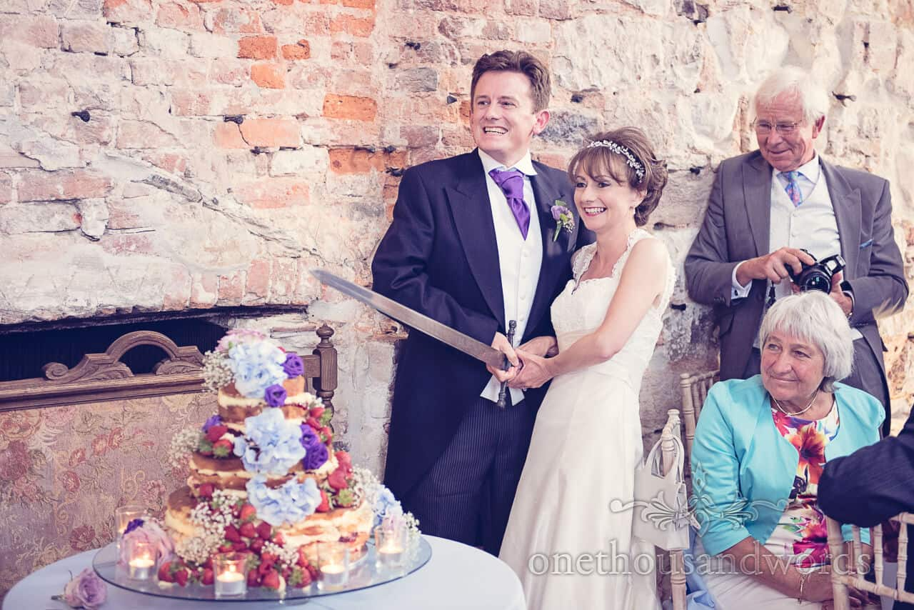 Cutting Cake Sword Lulworth Castle Wedding Photographers