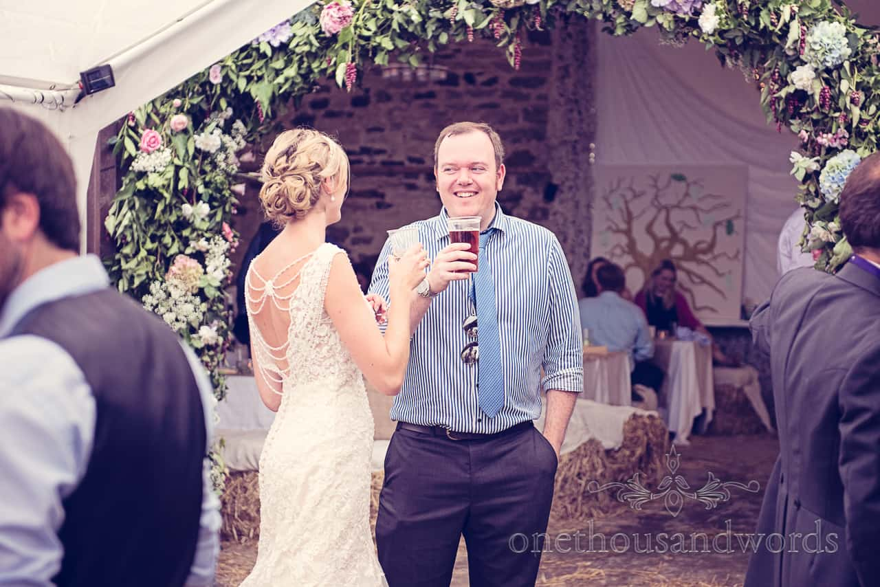 Wedding in Dorset guest enjoys a beer with bride
