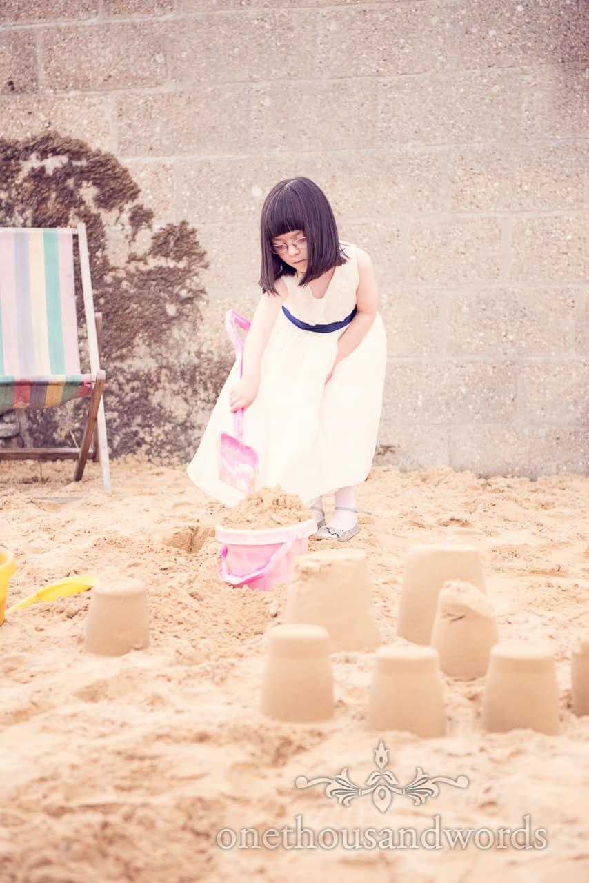 Flowergirl makes Sandcastles at Wedding in Dorset