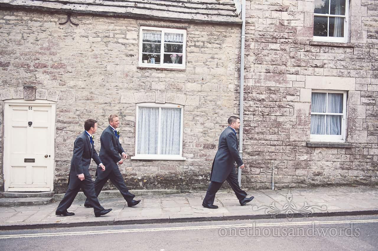 Groomsmen walk through Dorset village to church wedding