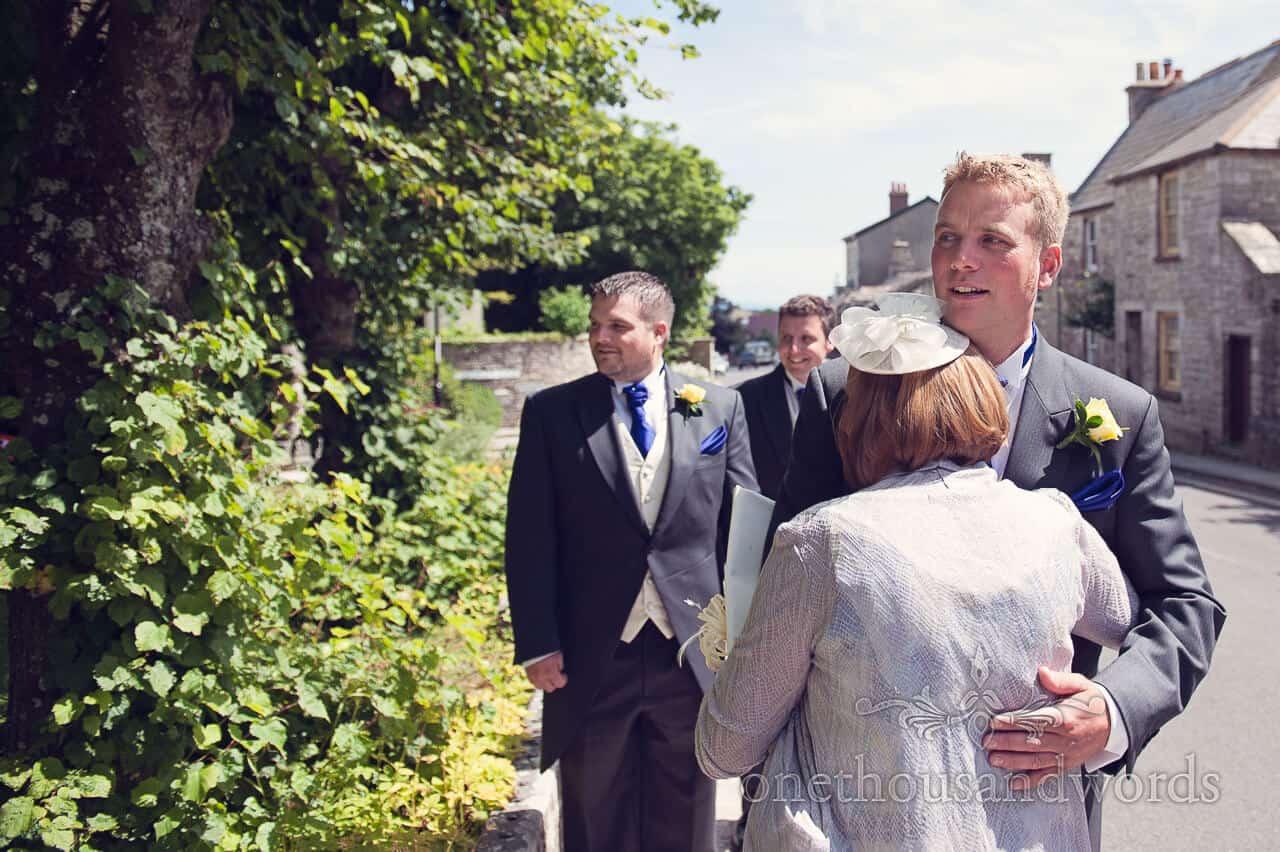 Mother of groom hugs groom before wedding service