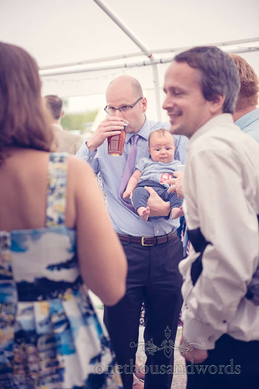 wedding in Dorset guest holds beer and baby!