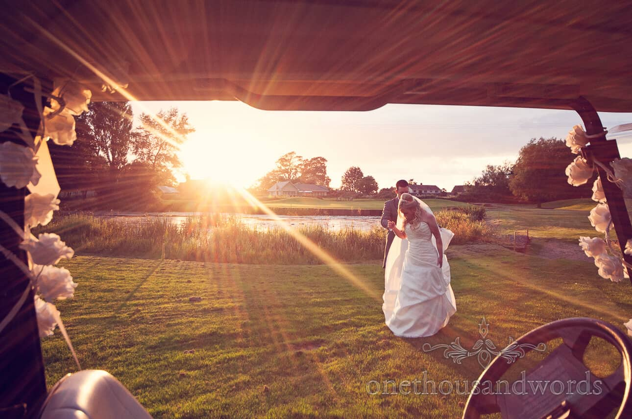 Sunset photograph of bride and groom through golf buggy