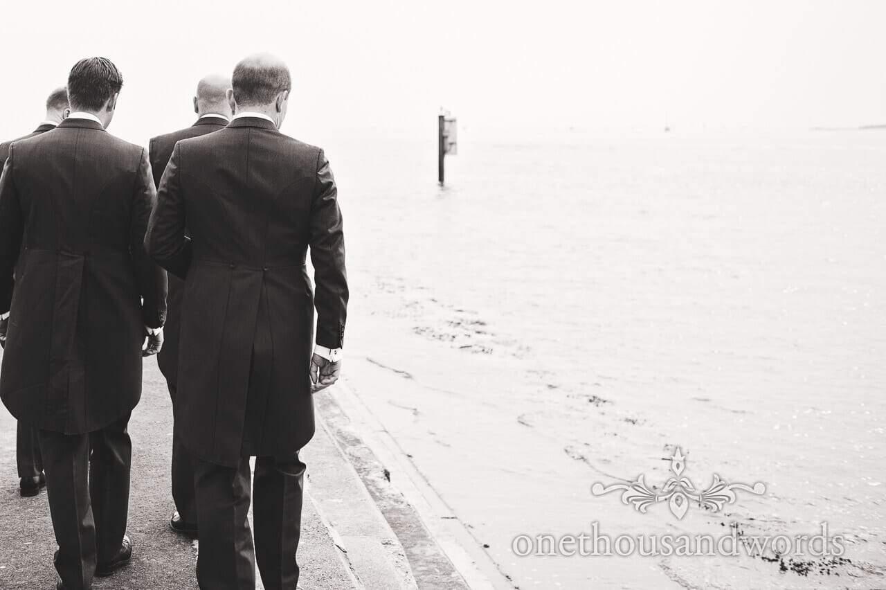 Groom and groomsmen walk at harbor entrance