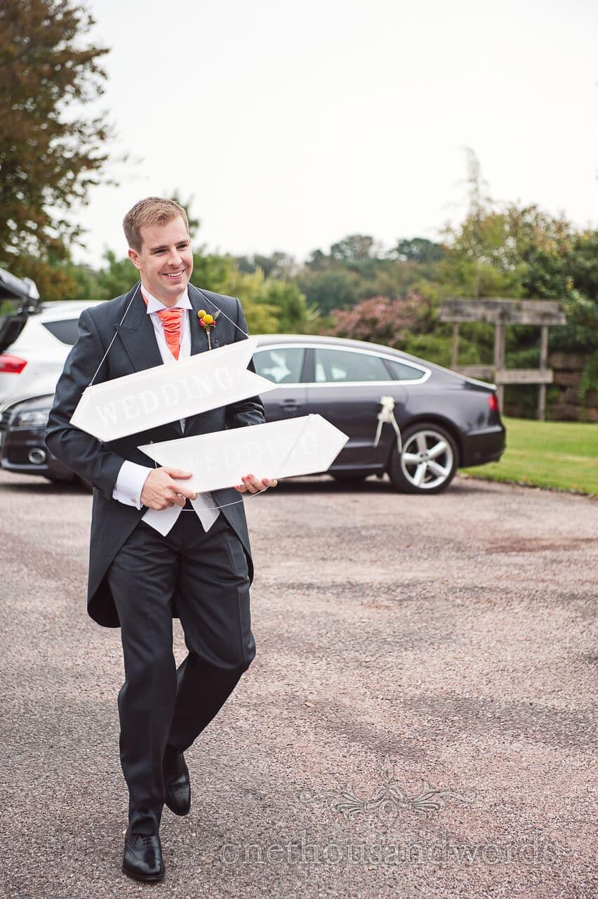 Groomsman with signs at Studland Bay House Wedding