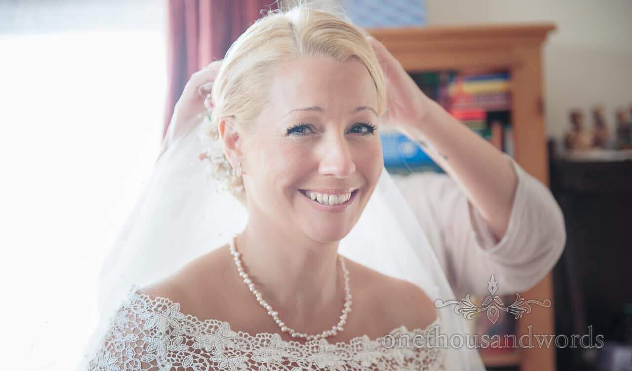 Blonde bride with pearl has veil added on wedding morning