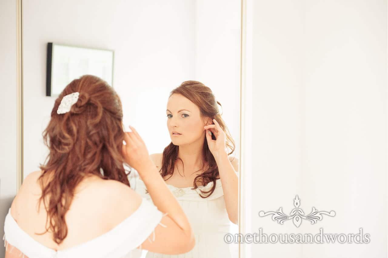 Bride adds wedding earrings in mirror