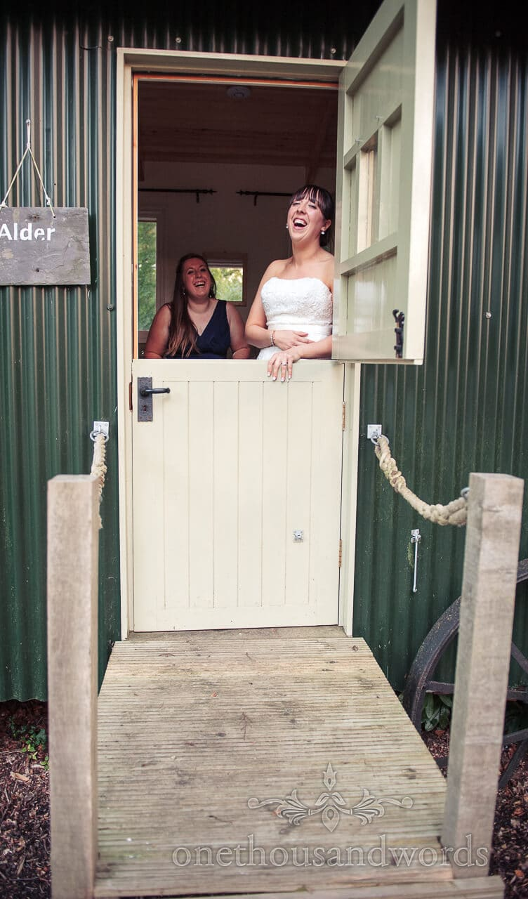 Bride and bridesmaid laugh in shepherds hut at weddigns in the wood