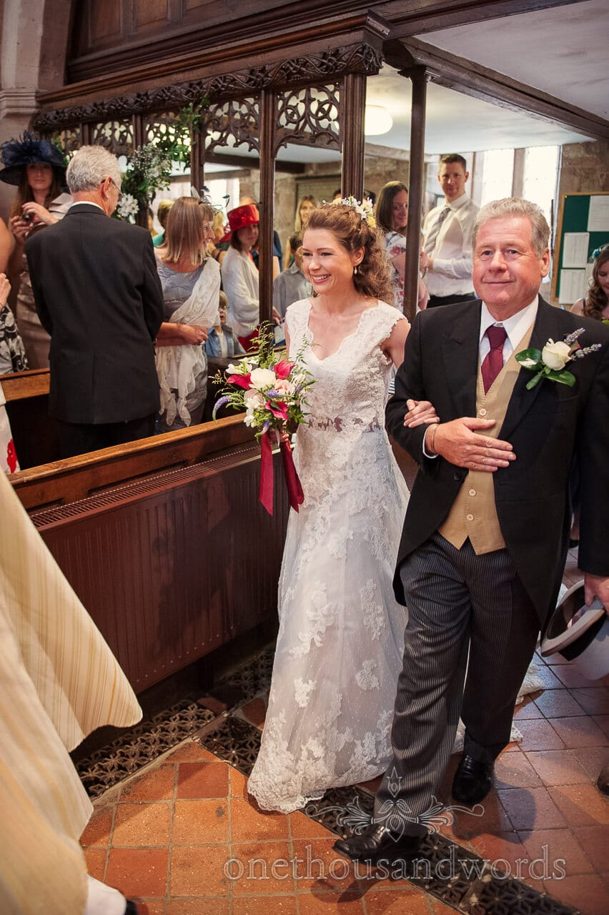 Bride and father of bride walk down church aisle