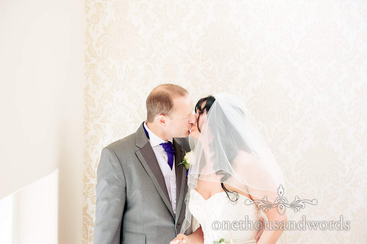 Bride and groom kissing against patterend wall paper in Dorset