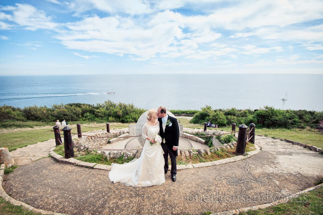 Bride and groom kiss by the sea at Durlston Castle Stone Globe